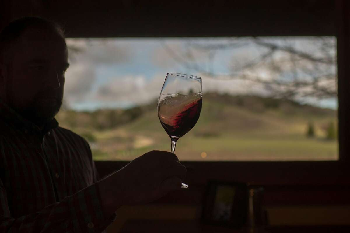 A customer swirls red wine at Thacher Winery tasting room in Paso Robles, Calif.