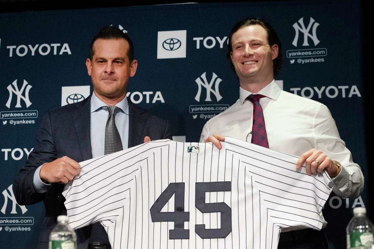 Yankees manager Aaron Boone, left, and pitcher Gerrit Cole hold up Cole's No. 45 as Cole is introduced by the team on Wednesdayin New York. The pitcher agreed to a 9-year, $324 million contract.