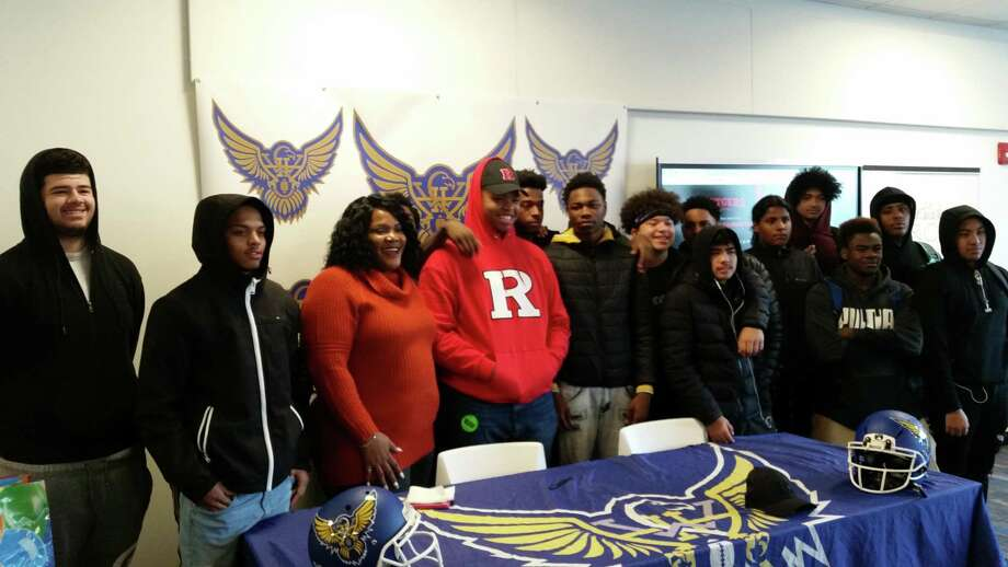 Harding senior lineman Troy Rainey poses with his mother, Portia, and his teammates after he signed his National Letter of Intent to play football at Rutgers. The ceremony was held at the school in Bridgeport, Conn., on Dec. 18, 2019. Photo: Michael Fornabaio / Hearst Connecticut Media