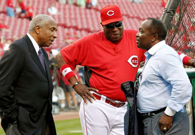 Cincinnati Reds manager Dusty Baker, center, talks with Hall of Fame players Frank Robinson, left, and Joe Morgan before Game 3 of the National League Division Series baseball game against the Philadelphia Phillies Sunday, Oct. 10, 2010, in Cincinnati. (AP Photo/Gene J. Puskar)