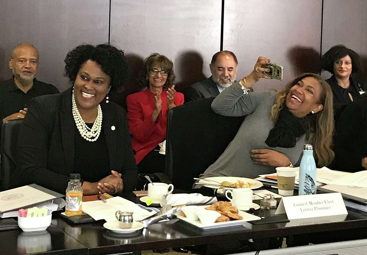 Councilmember Martha Castex-Tatum and Council member-elect Letitia Plummer laugh as Plummer snaps a picture during the second day of orientation for newly elected council members on Tuesday, Dec. 17, 2019, in a conference room at the George R. Brown Convention Center.