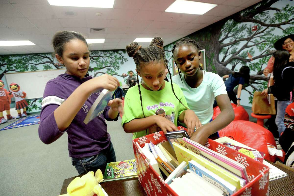 From left, Harmoni Willaims, Zay'Lyn Pleasant and Trinity Davis check out some of their new books after Lamar University staff senate members and Dr. Ken Evans presented a boxful of new books for The N.E.S.T. (Navigating Excellence Success and Triumph) at Pietzsch-MacArthur Elementary School, which was the first N.E.S.T. reading room created through a joint effort by Principal Audrey Collins and the late first lady Nancy Evans as part of a Lamar-based community enrichment effort supporting area schools and children. There are now three schools that have N.E.S.T.s - Charlton-Pollard and Blanchette Elementaries were the latest additions, with plans for future sites to be created at other BISD elementary campuses. Photo taken Wednesday, December 18, 2019 Kim Brent/The Enterprise