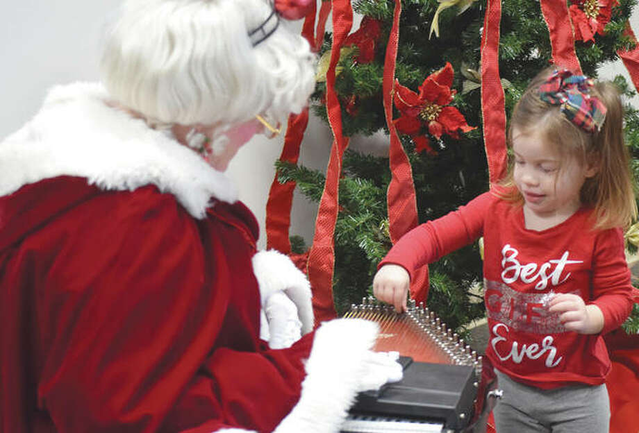 Mrs. Claus lets Addison Attanasio, 2, of Jacksonville play her autoharp Wednesday during a Cocoa with Mrs. Claus event at Jacksonville Public Library. Photo: Marco Cartolano | Journal-Courier