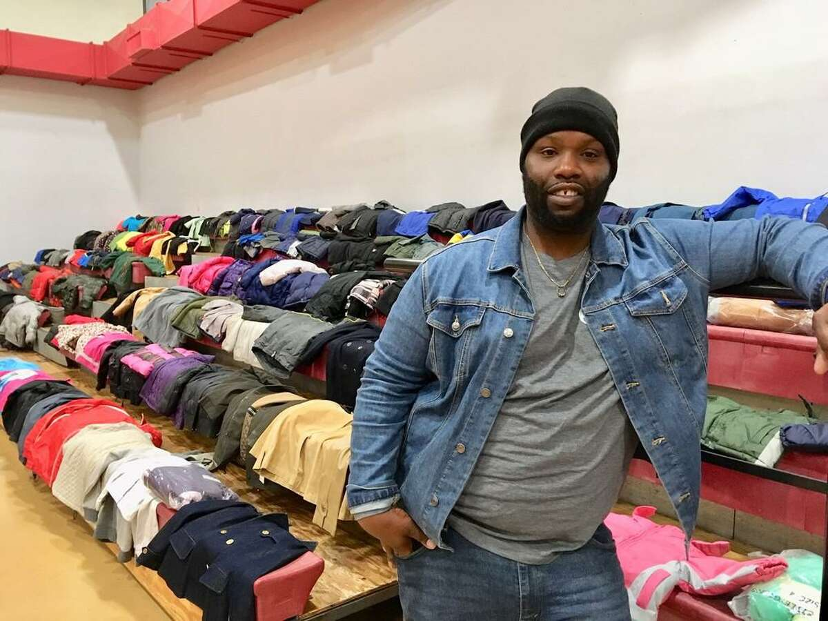 Harry Bell of Color a Positive Thought stands in front of the winter coats that will be given away Saturday in Bridgeport. Dec. 17, 2019