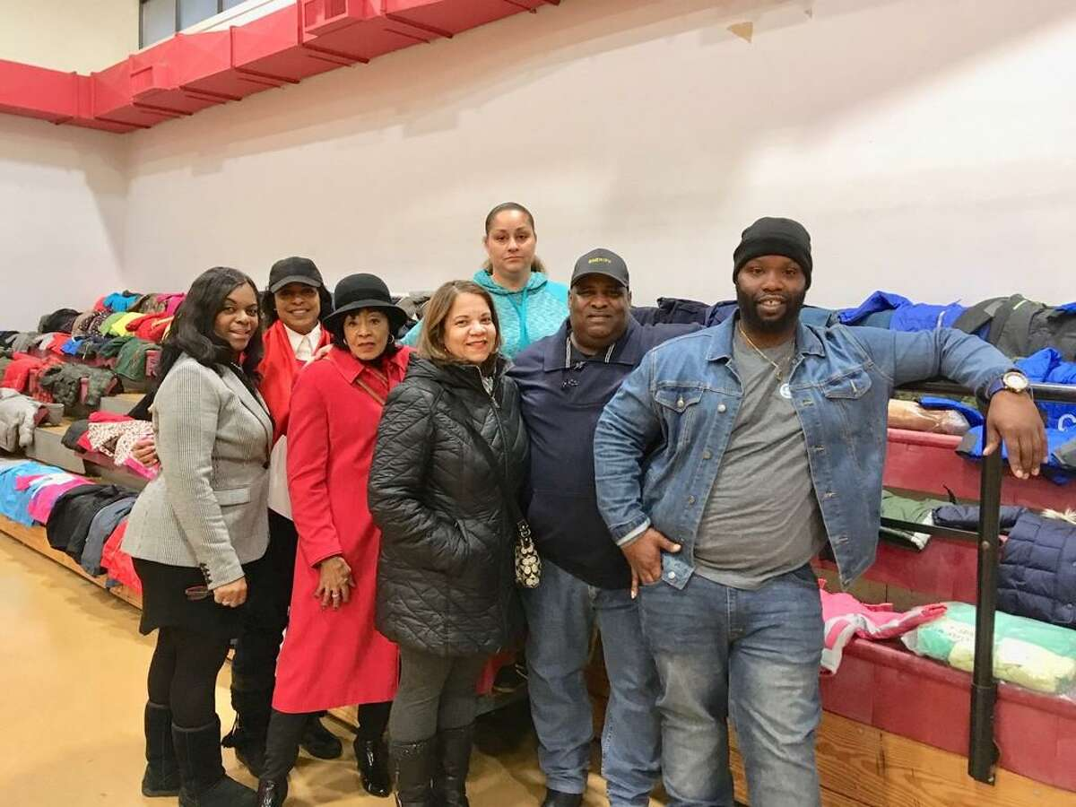 Harry Bell of Color a Positive Thought, along with the We Care committee stand in front of the Warm the City coats that will be distributed Saturday in Bridgeport. Dec. 17, 2019