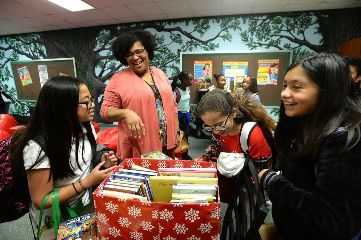Principal Audrey Collins jokes with Isabella Hoang as they and other students dig into the reading materials brought by Lamar University staff senate members and Dr. Ken Evans for The N.E.S.T. (Navigating Excellence Success and Triumph) at Pietzsch-MacArthur Elementary School, which was the first N.E.S.T. reading room created through a joint effort by Principal Audrey Collins and the late first lady Nancy Evans as part of a Lamar-based community enrichment effort supporting area schools and children. There are now three schools that have N.E.S.T.s - Charlton-Pollard and Blanchette Elementaries were the latest additions, with plans for future sites to be created at other BISD elementary campuses. Photo taken Wednesday, December 18, 2019 Kim Brent/The Enterprise