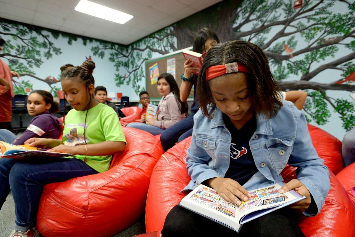 Zay'Lyn Pleasant (left) and Kaylei Lewis check out some of their new books after Lamar University staff senate members and Dr. Ken Evans presented a boxful of new books for The N.E.S.T. (Navigating Excellence Success and Triumph) at Pietzsch-MacArthur Elementary School, which was the first N.E.S.T. reading room created through a joint effort by Principal Audrey Collins and the late first lady Nancy Evans as part of a Lamar-based community enrichment effort supporting area schools and children. There are now three schools that have N.E.S.T.s - Charlton-Pollard and Blanchette Elementaries were the latest additions, with plans for future sites to be created at other BISD elementary campuses. Photo taken Wednesday, December 18, 2019 Kim Brent/The Enterprise