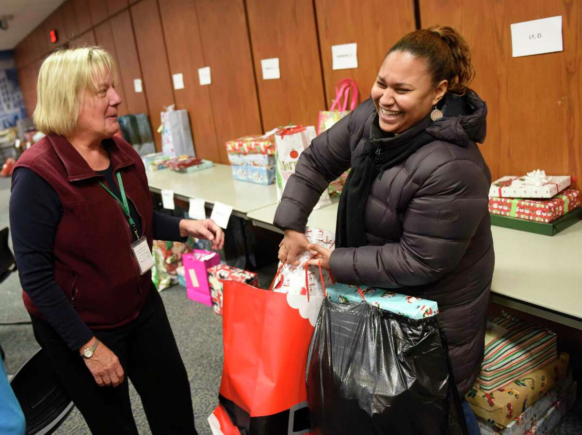 Greenwich resident Polkha Morel, right, receives holiday gifts from Department of Human Services community gifts program coordinator Alison Brush at the annual Angel Tree gift giving program at Town Hall in Greenwich, Conn. Wednesday, Dec. 18, 2019. The Department of Human Services program provided 625 holiday gifts for 200 families thanks to donations from six local groups.
