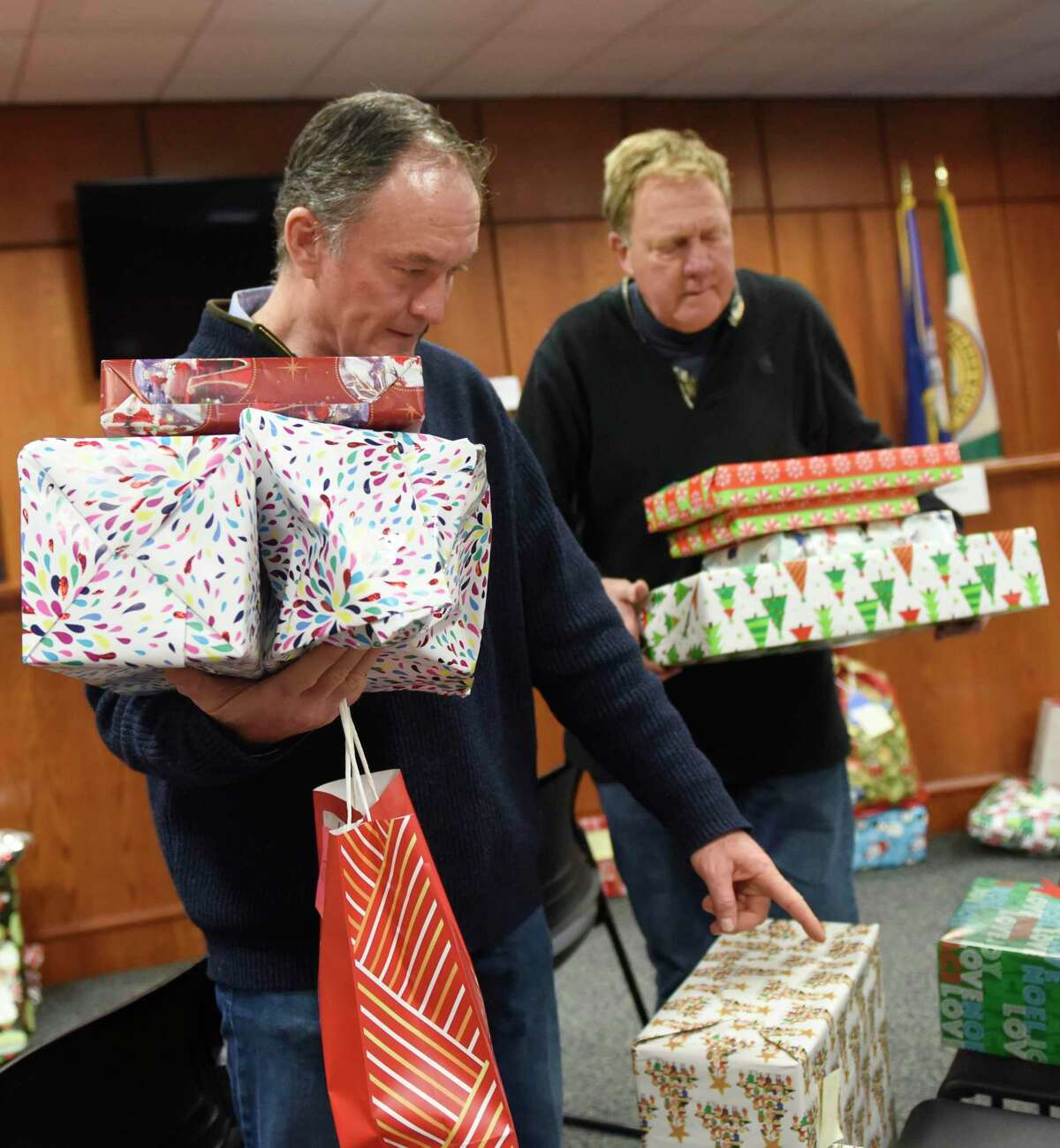 Department of Human Services volunteers Fernando Ruiz, left, and Rod Brush distribute presents for the annual Angel Tree gift giving program at Town Hall in Greenwich, Conn. Wednesday, Dec. 18, 2019. The Department of Human Services program provided 625 holiday gifts for 200 families thanks to donations from six local groups.