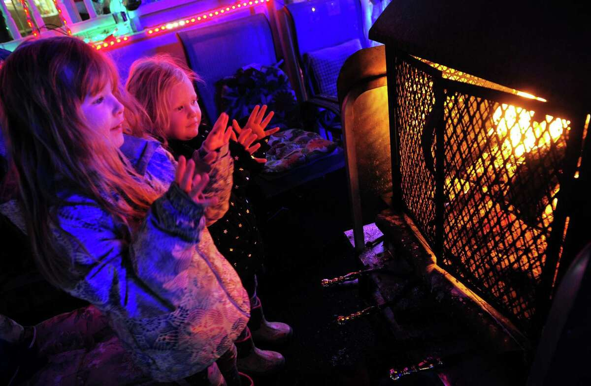 Charlotte Baxley, 6, of Bridgeport, and her little sister Emma, 3, pause to get warm by the fire at the Wonderland at Roseville, a spectacular Christmas display, on Roseville Terrace in Fairfield, Conn., on Wednesday Dec. 18, 2019.