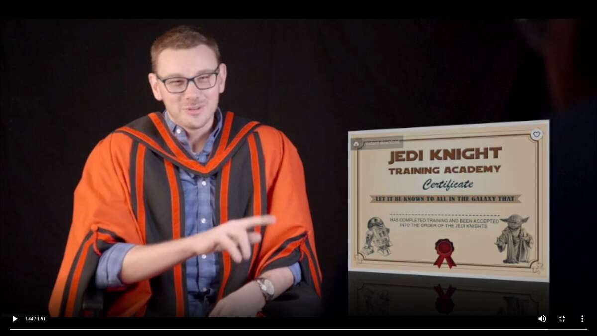 A graphic playfully mocks Steve Axon's Jedi knight certification in a still from the video.