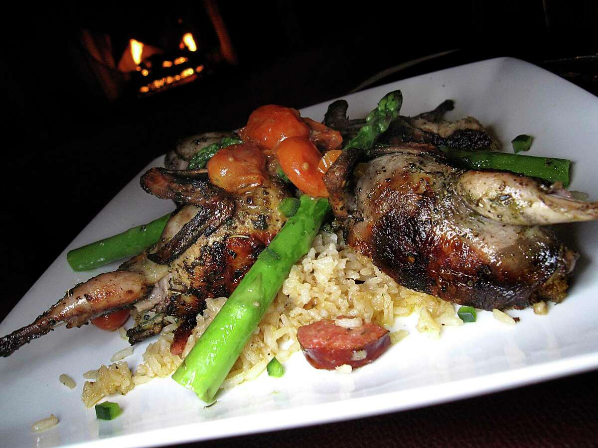 Grilled quail is stuffed with andouille sausage stuffing and served with Cajun dirty rice and asparagus at Iron Stag.