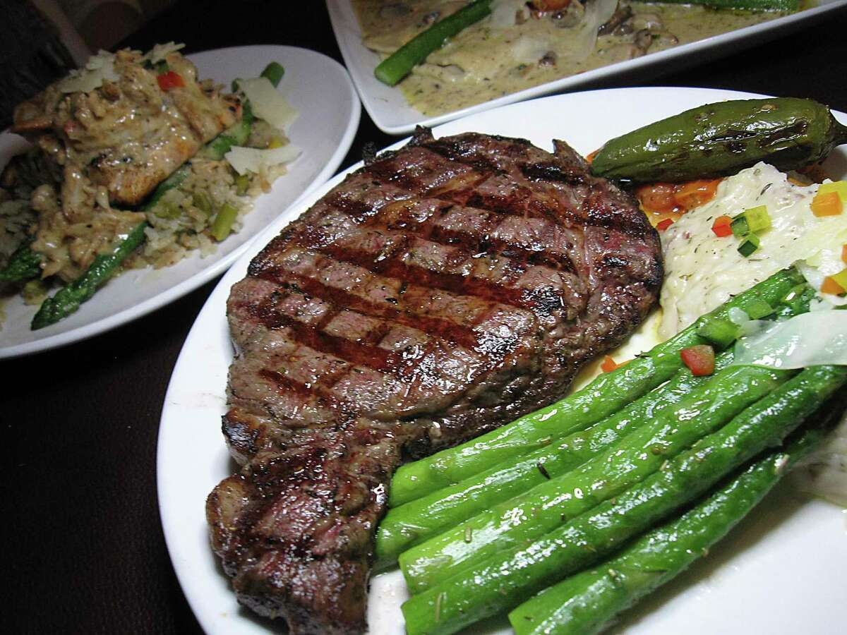 Entrees include a grilled rib-eye steak, salmon with shrimp and crab and mushroom ravioli at Iron Stag.