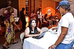 Ilsa Nieves of the American Job Center Workforce Alliance, left, pre-registers people for interviews for approximately 1800 Amazon North Haven warehouse facility openings during a job fair in New Haven, Conn., on Aug. 30, 2019. Connecticut has gained 13,300 jobs in the past year, including 4,000 in February 2020.