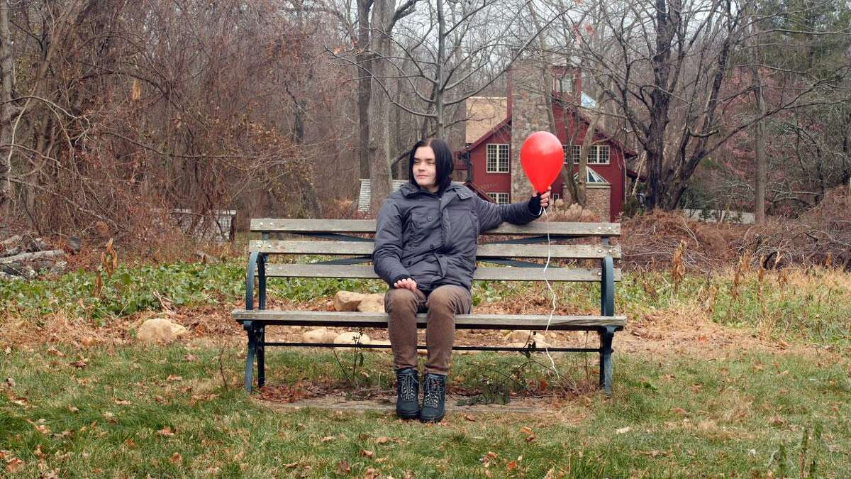 """Guy, played by Jac Bernhard, and Harold (the balloon) relax on the """"friendship bench"""" at Stonebridge Waterfowl Preserve in Wilton in a scene from """"You Can Buy Love From the Dollar Store,"""" by filmmaker Vik Zoeller."""