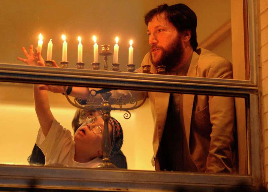 Rabbi Jon-Jay Tilsen helps religious school student Jacob Botwick-Ries of New Haven, 9, light the menorah as Tilsen explained the meaning of the menorah lighting at the Congregation Beth El-Keser Israel in New Haven in 2006. Photo: Hearst Connecticut Media File