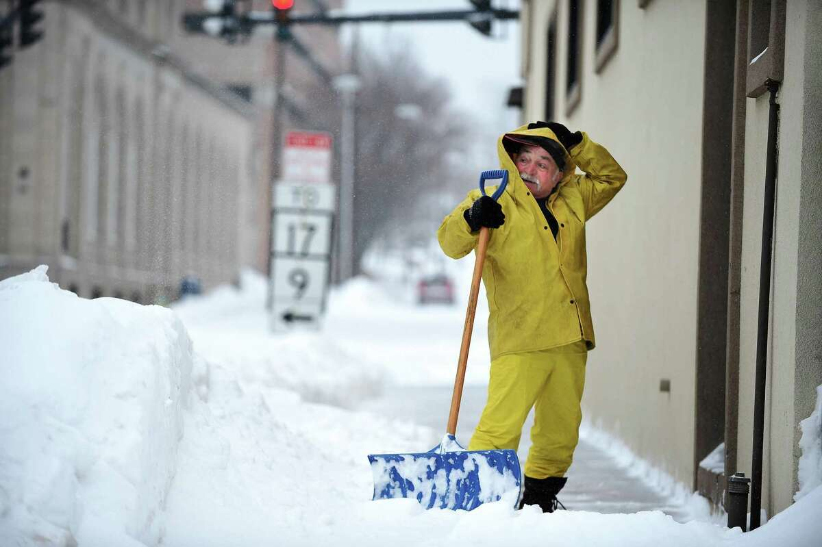 Dominic Guiliano of Middletown pauses to adjust his hood while shoveling the sidewalk during a February 2015 snowstorm.