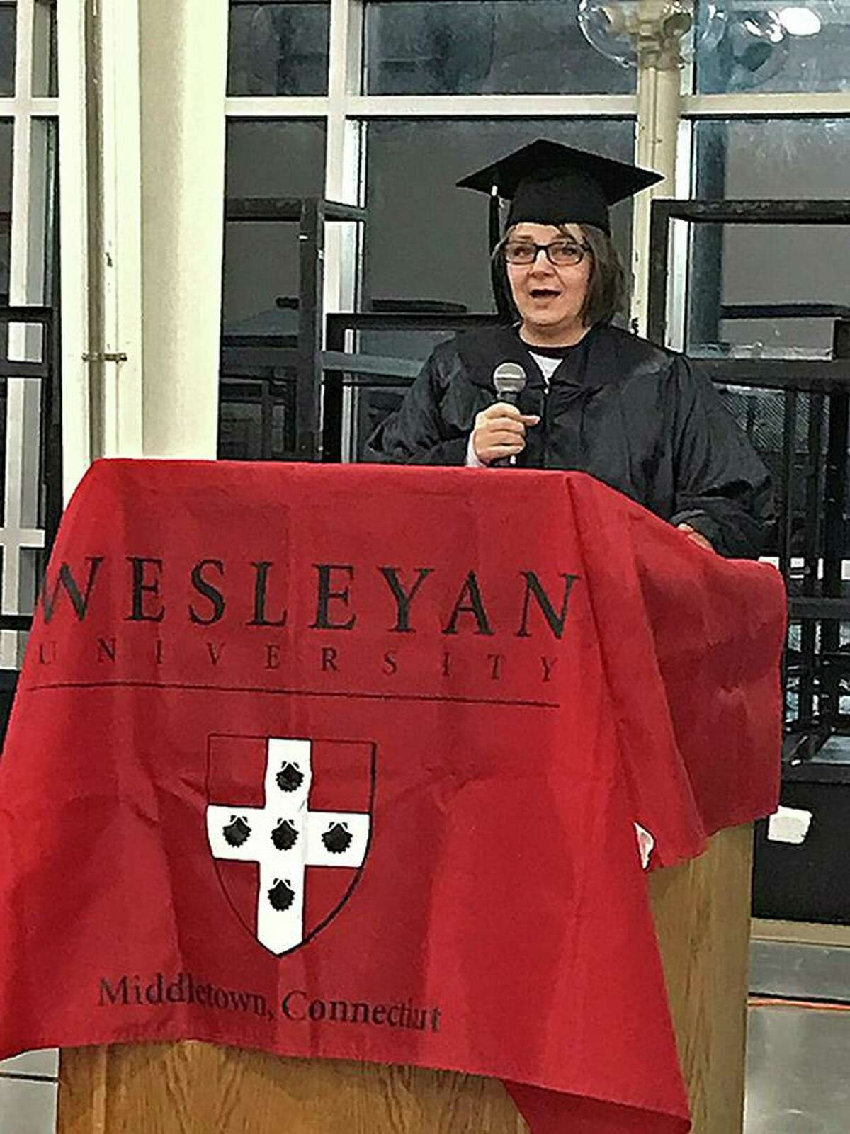 Tracy Shumaker, one of the seven women who received her associate's degree Tuesday from Wesleyan University's Center for Prison Education, addresses audience members during graduation at the York Correctional Institution in Niantic.