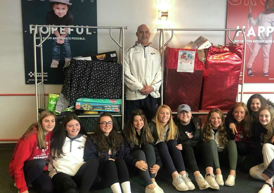 New Fairfield's Grace Fritzsche, center, is surrounded by her classmates and coach Greg Schwarz after donating toys to Connecticut Children's Medical Center on Wednesday. Photo: Ryan Lacey/Hearst Connecticut Media