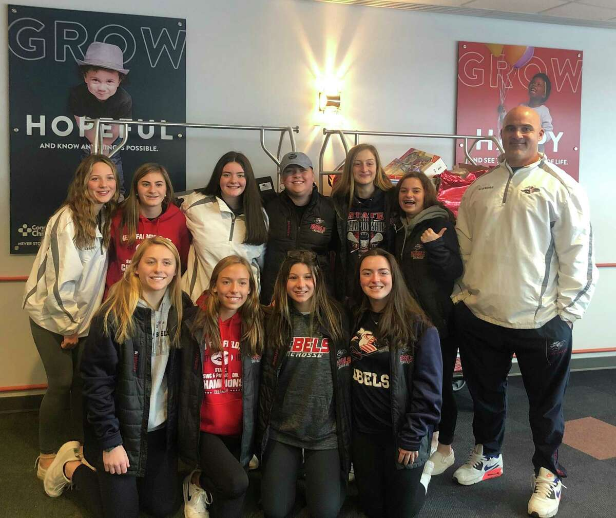 New Fairfield's Grace Fritzsche, center, is surrounded by her classmates and coach Greg Schwarz after donating toys to Connecticut Children's Medical Center on Wednesday.