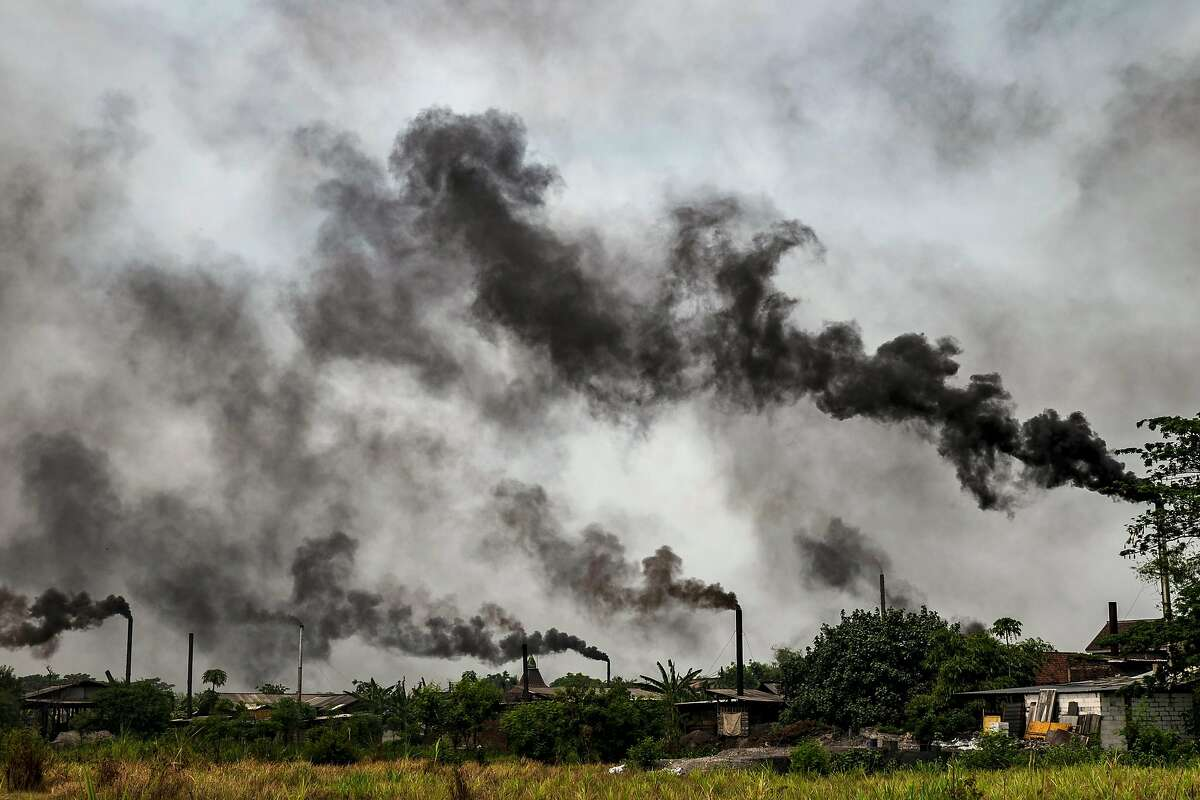 FILE -- Black smoke, caused by burning plastic as fuel at a tofu factory, is seen in Tropodo, Indonesia, on Nov. 2, 2019. The Indonesian government, stung by a report that found burning plastic for fuel is poisoning residents in an East Java village, is allowing the illegal burning to continue while it challenges the environmental study. (Ulet Ifansasti/The New York Times)