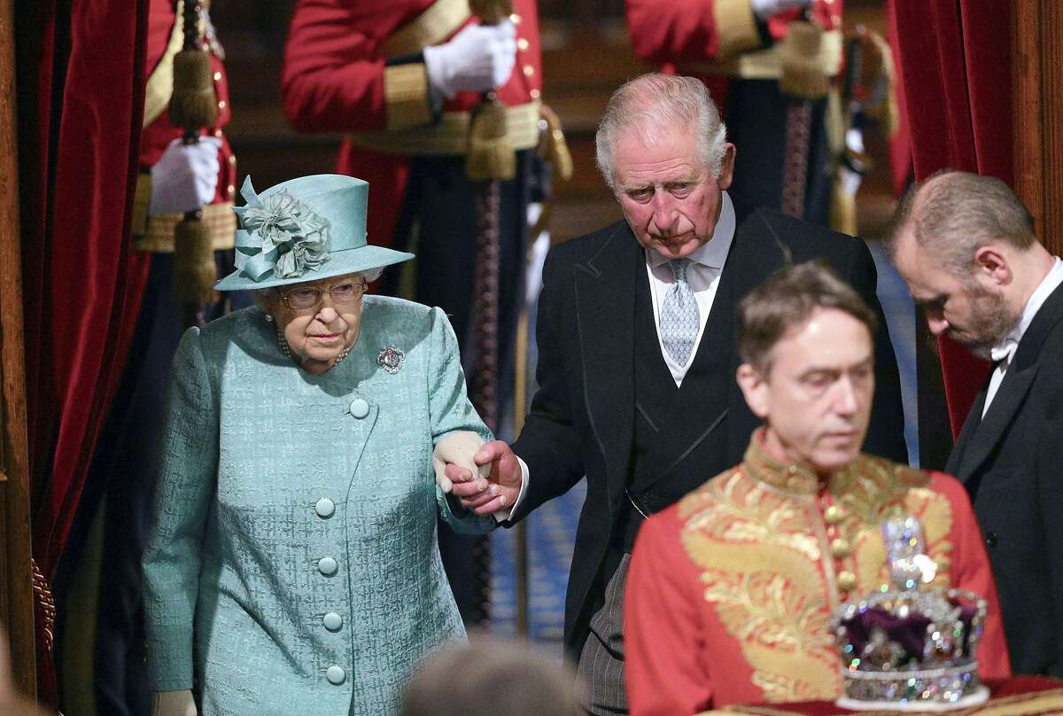 Britain's Queen Elizabeth II and Prince Charles walk behind the Imperial State Crown as they arrive in the chamber for the State Opening of Parliament, in the House of Lords at the Palace of Westminster in London, Thursday Dec. 19, 2019. Queen Elizabeth II will formally open a new session of Britain's Parliament on Thursday, with a speech giving the first concrete details of what Prime Minister Boris Johnson plans to do with his commanding House of Commons majority. (Aaron Chown, Pool via AP)