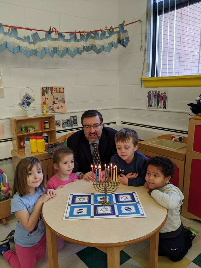 Rabbi Colin Brodie lights the Hanukkah menorah with B'nai Torah Nursery School students. Photo: Contributed Photo