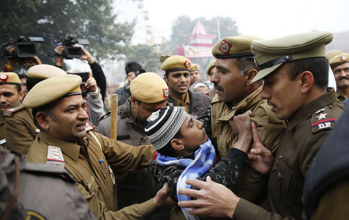 A young protestor tries to resist as police officers detain him during a march near the historic Red Fort in New Delhi, India, Thursday, Dec. 19, 2019. Police detained several hundred protestors in some of India's biggest cities Thursday as they defied a ban on assembly that authorities imposed to stem widespread demonstrations against a new citizenship law that opponents say threatens India's secular democracy. Dozens of demonstrations were to take place around country as opposition grows to a new citizenship law that excludes Muslims. The law has sparked anger at what many see as the government's push to bring India closer to a Hindu state. (AP Photo/Altaf Qadri)