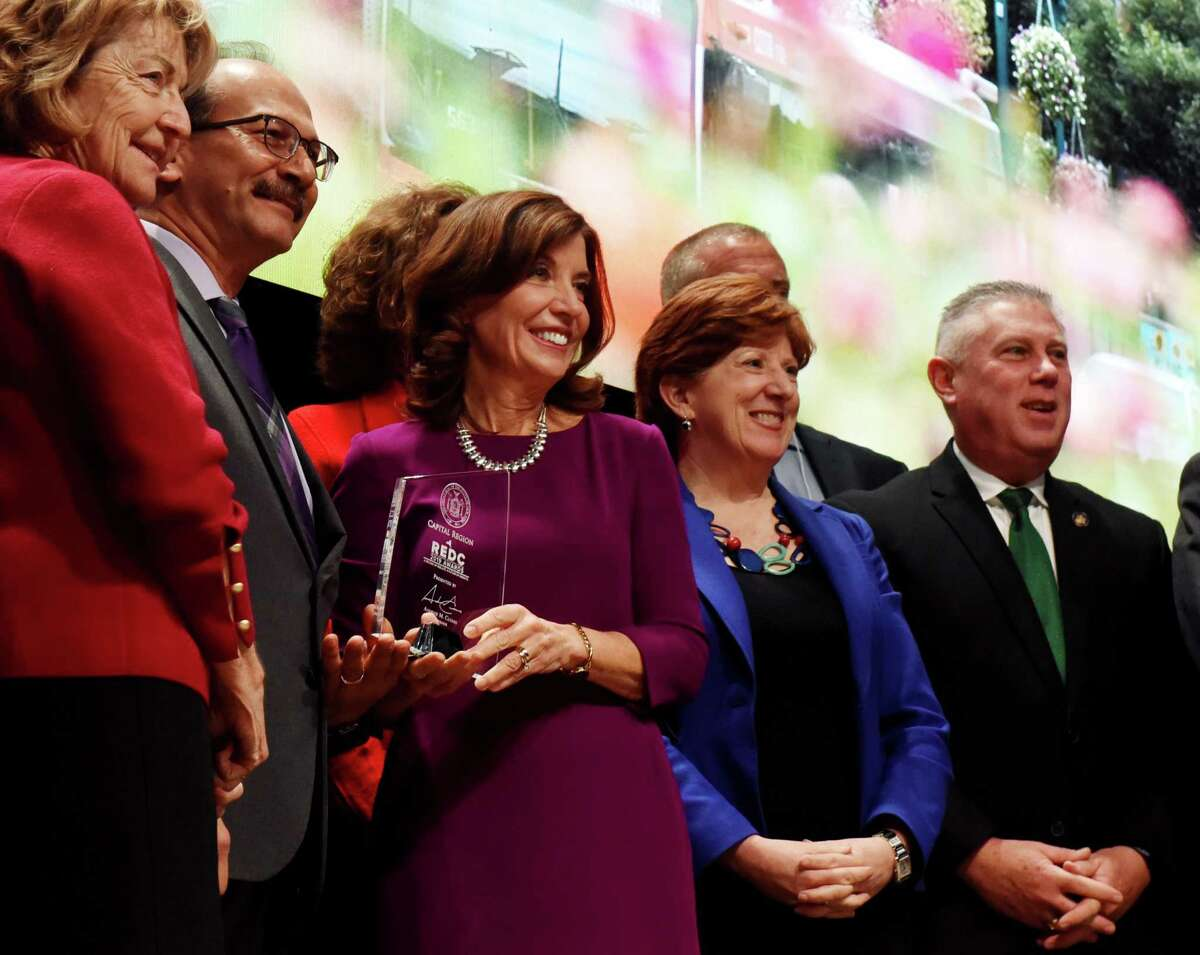 Sen. Betty Little, left, University at Albany President Havidán Rodríguez, Mayor Kathy Sheehan, second from right, and Assemblyman John T. McDonald III, right, and other Capital Region representatives, pose for a photo with Lt. Gov. Kathy Hochul, center, after the district was awarded $84.1 million by the state for economic development on Thursday, Dec. 19, 2019, during the Regional Economic Development Council awards ceremony at the Capital Center in Albany, N.Y. (Will Waldron/Times Union)