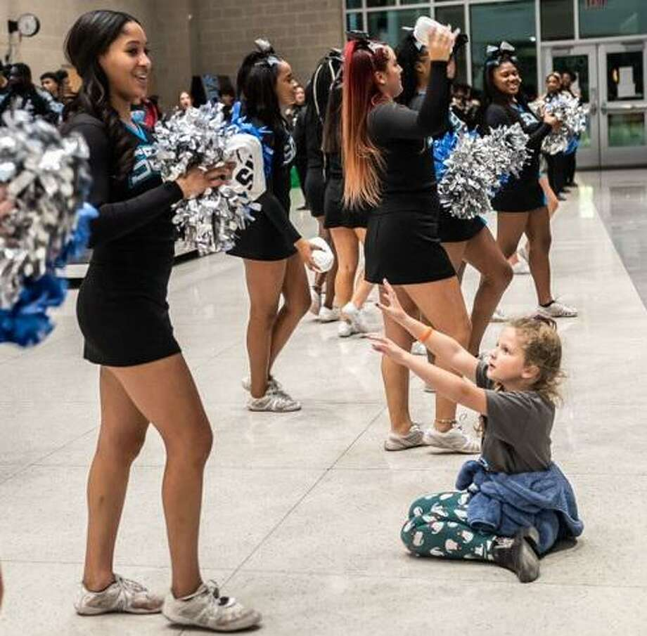 Isabelle Johnson, 8, right, gets into a Shadow Creek High pep rally before the championship game. She is among area residents excited by the sports success achieved by the young school. Photo: Kim Christensen / Contributor