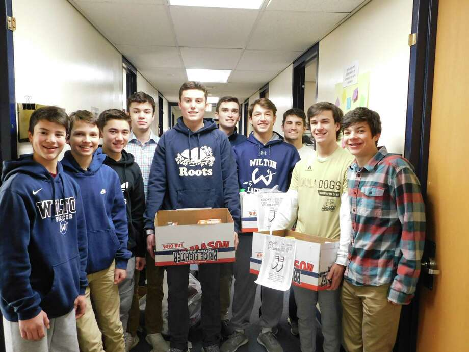 Socks for Soldiers club members, from left, Tyler Casey, Sam Gioffre, Ryan Leung, James Vollmer, Jack Savarese. Roen Crameri, Jake Zeyher, Dom Polito, Connor Burke, and Eli Ackerman get ready to deliver their Christmas collection of socks. Photo: Contributed Photo / Wilton High School / Wilton Bulletin Contributed