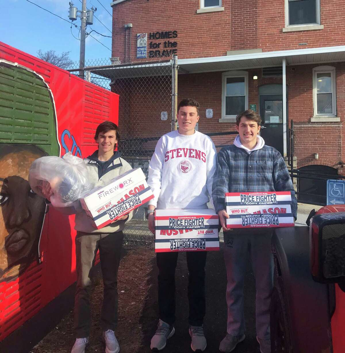 Socks for Soldiers program coordinators Connor Burke, left, Jack Savarese and Jake Zeyher deliver their Christmas collection of socks to Homes for the Brave in Bridgeport on Dec. 19.