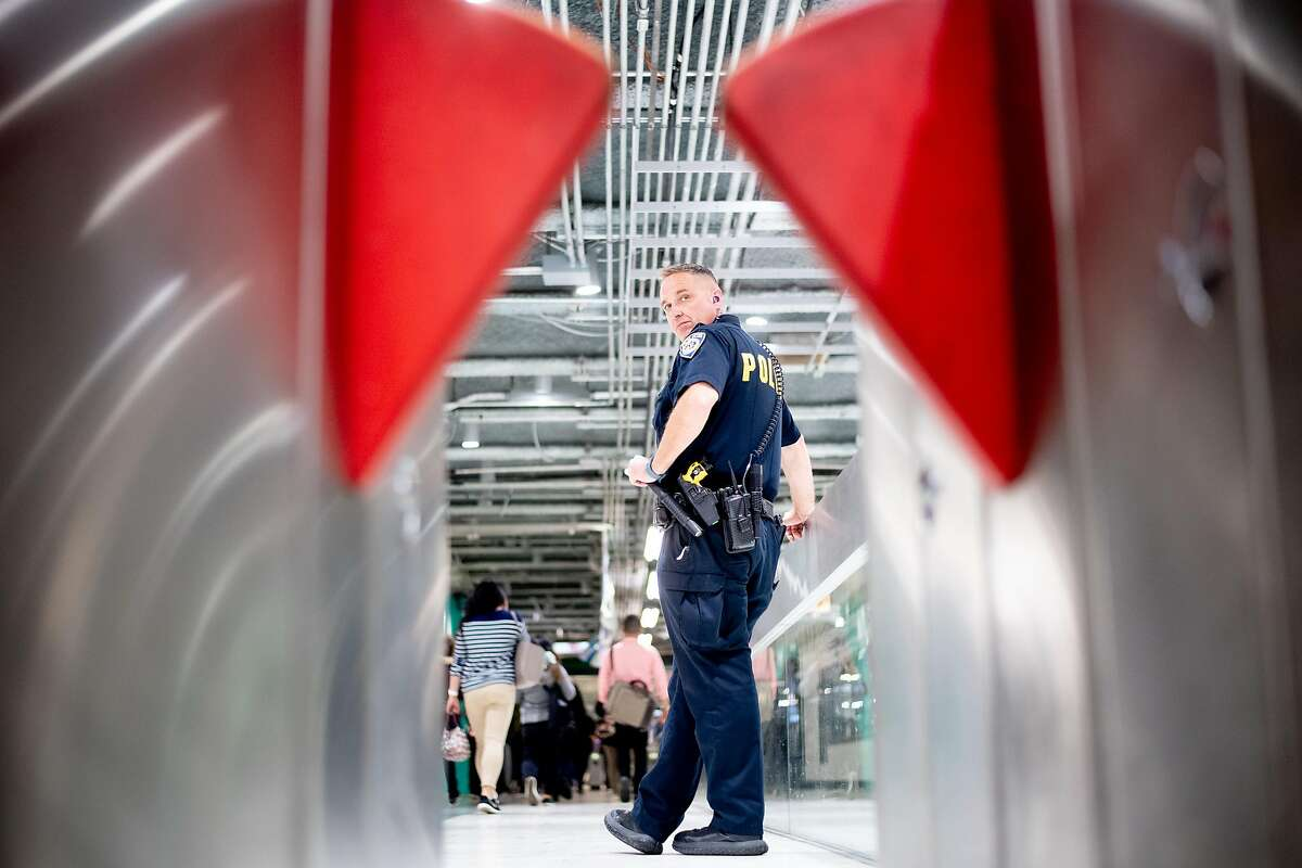 BART police Officer Zwetsloot watches for fare evaders at the Powell Street station on Wednesday, June 5, 2019, in San Francisco. Beginning in April, BART police officers and fare inspectors increased efforts to catch fare evaders who cost the system millions.