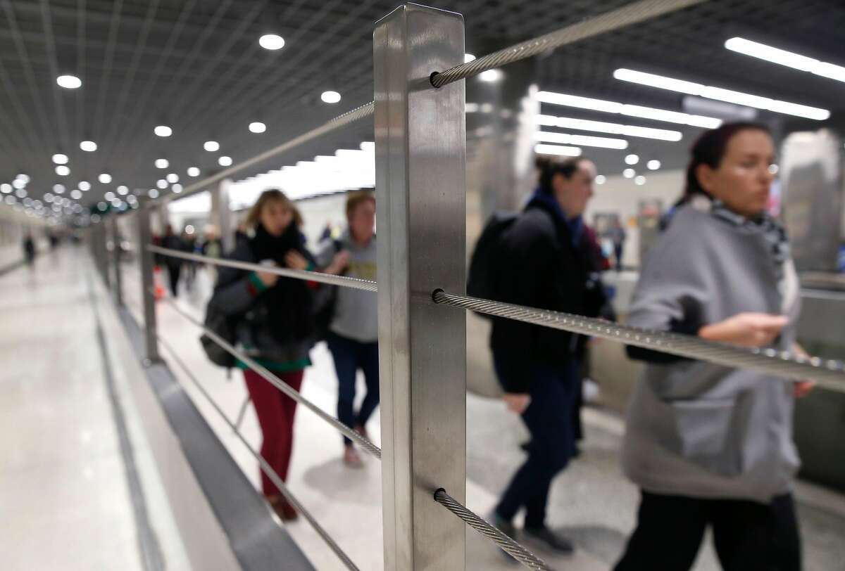 Commuters walk past a railing with enhancements recently installed to thwart fare cheats at the Powell Street BART station in San Francisco, Calif. on Thursday, Dec. 19, 2019. BART is stepping up efforts to reduce fare evasion.