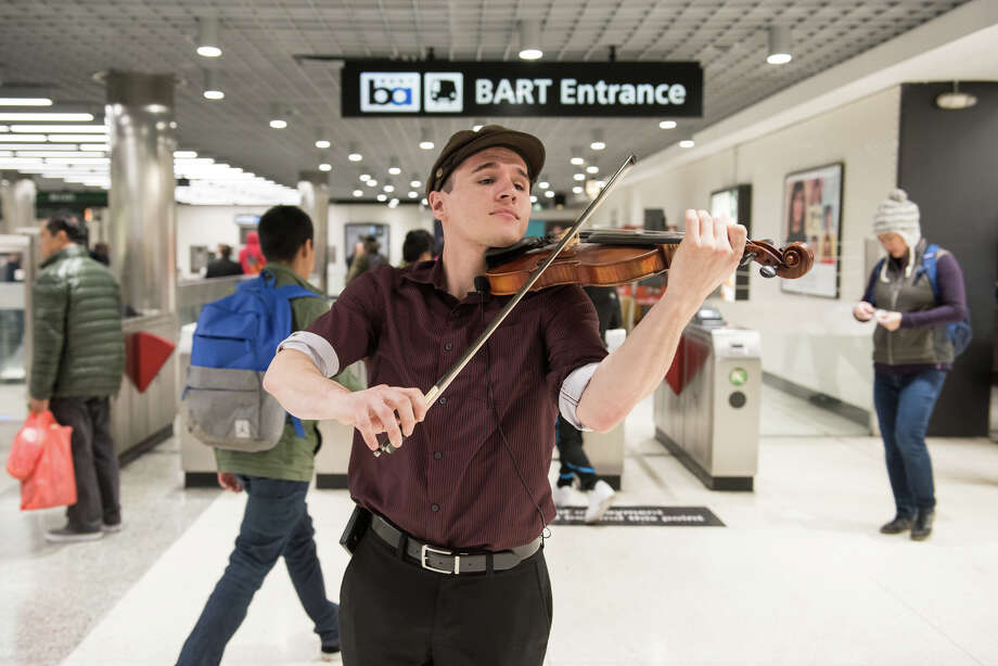 In his spare time, John Bridenbeck is a busker in the Bay Area.  Here he performs for commuters at the BART Powell St. station. Photo: Blair Heagerty / SFGate