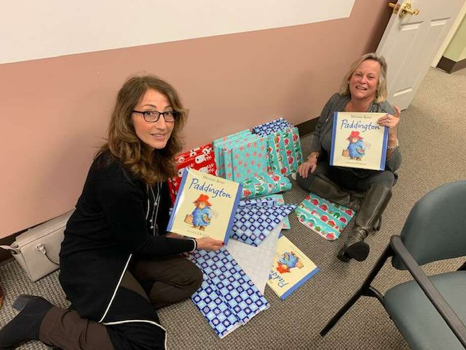 Ridgefield realtors Toni Riordan, left and Mary Pat Sexton, right spent time at the CT Coalition to End Homelessness office in Hartford last week wrapping Paddington bears, books and blankies that were delivered to children living in shelters across Connecticut for the holidays. Photo: Contributed Photo