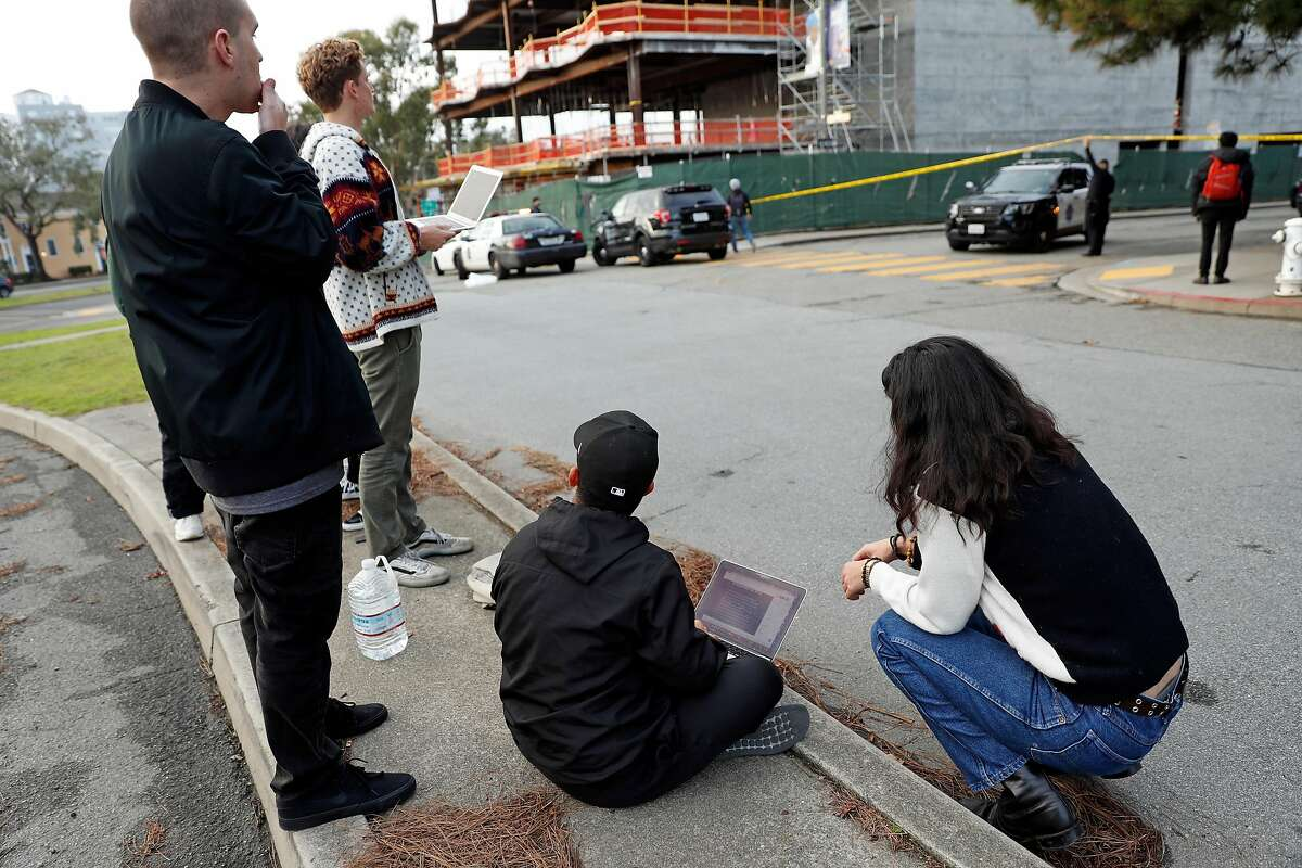 Members of the Golden Gate XPress, the San Francisco State University student newspaper, stand in the middle of Holloway Avenue as they report on a bomb threat at SFSU in San Francisco, Calif., on Thursday, December 19, 2019.