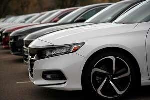 A long row of unsold 2020 Accord sedans sits at Honda dealership.