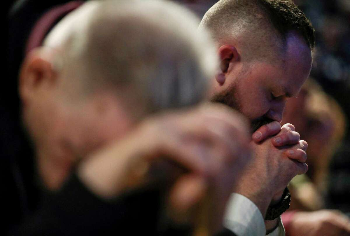 People pray on the second day of the Southern Baptist Convention's annual meeting on Wednesday, June 12, 2019, in Birmingham, Ala.