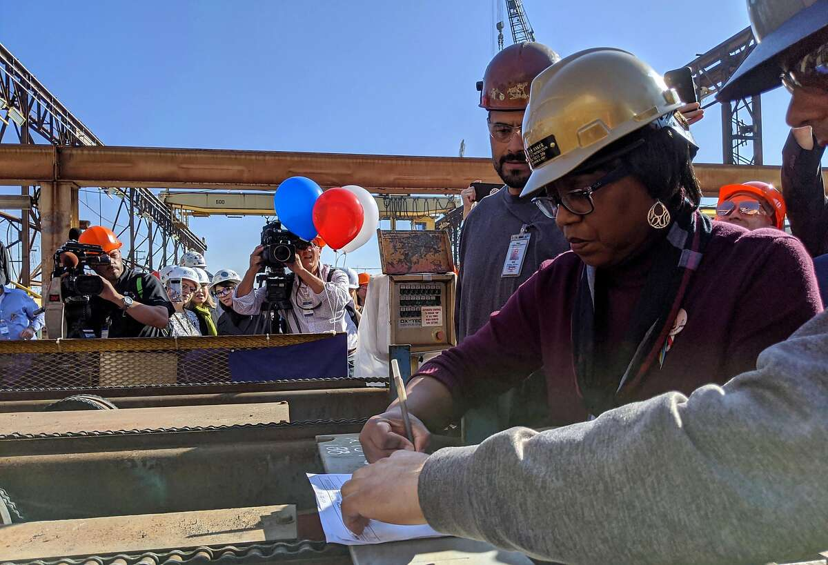 Kathy Baker, center, a logistics engineer with 45 years at NASSCO, signs off on the ceremonial first cut of steel for the future USNS Harvey Milk on Friday at General Dynamics NASSCO in San Diego.