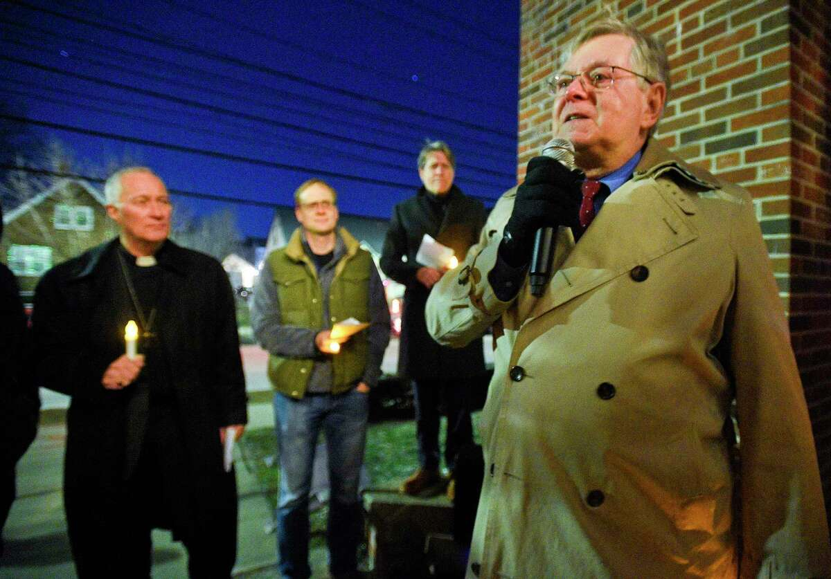 Stamford Mayor David Martin stands with others as they hold a candle light vigil during a Homeless Persons' Memorial Service at the Bethel AME Church in Stamford, Conn. on Dec. 19, 2019.