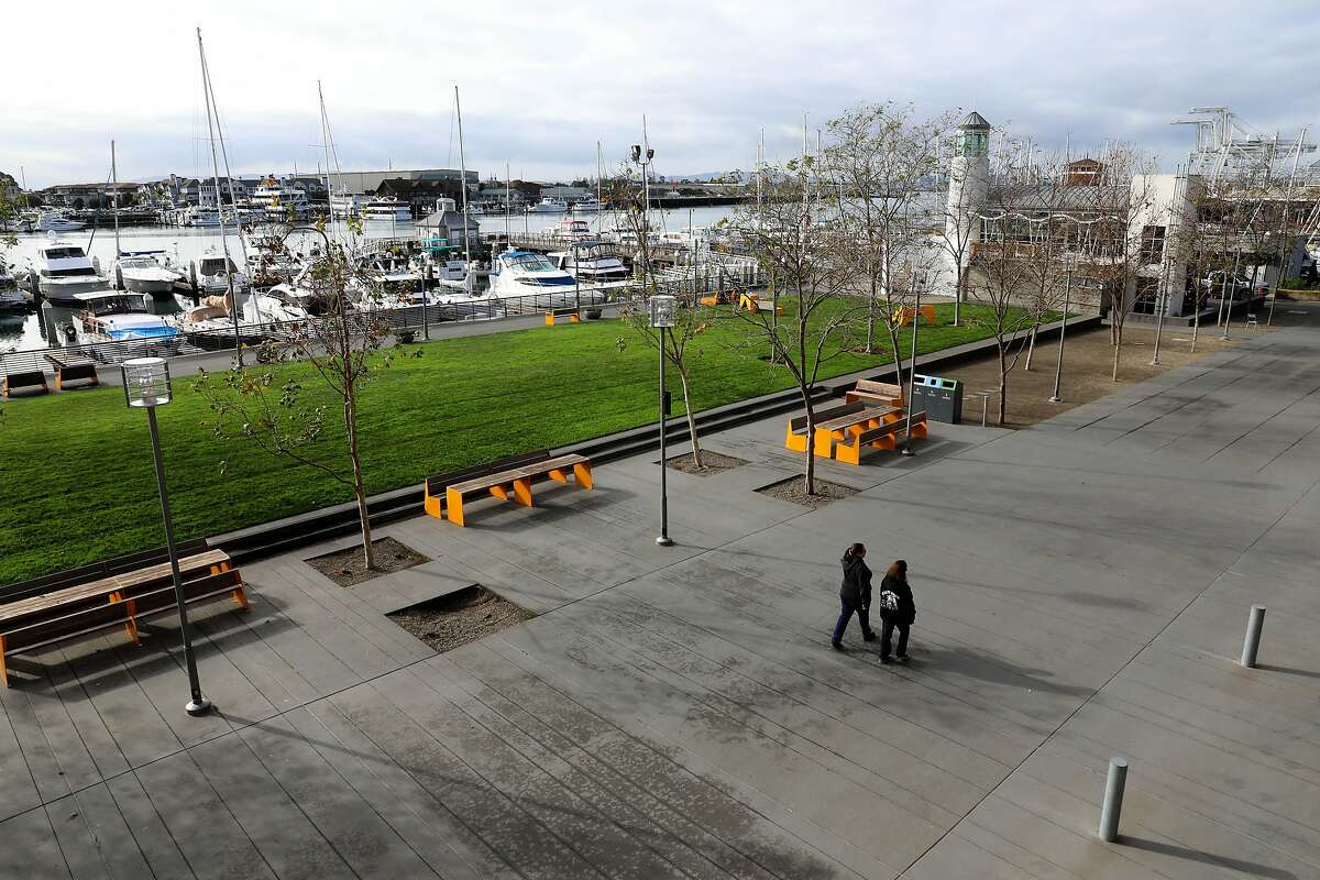 People walk on the Jack London Square promenade in Oakland, Calif., on Thursday, December 19, 2019.