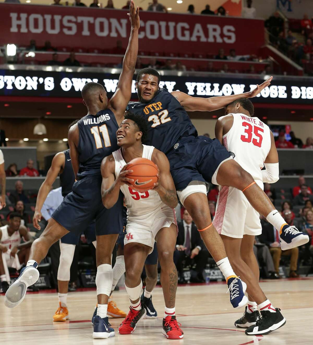 Houston center Brison Gresham (55) tries to push up against UTEP forward Bryson Williams (11) and forward Efe Odigie (32) as they fall on him going for the rebound during the second half of their game Thursday, Dec. 19, 2019 in Houston, TX.