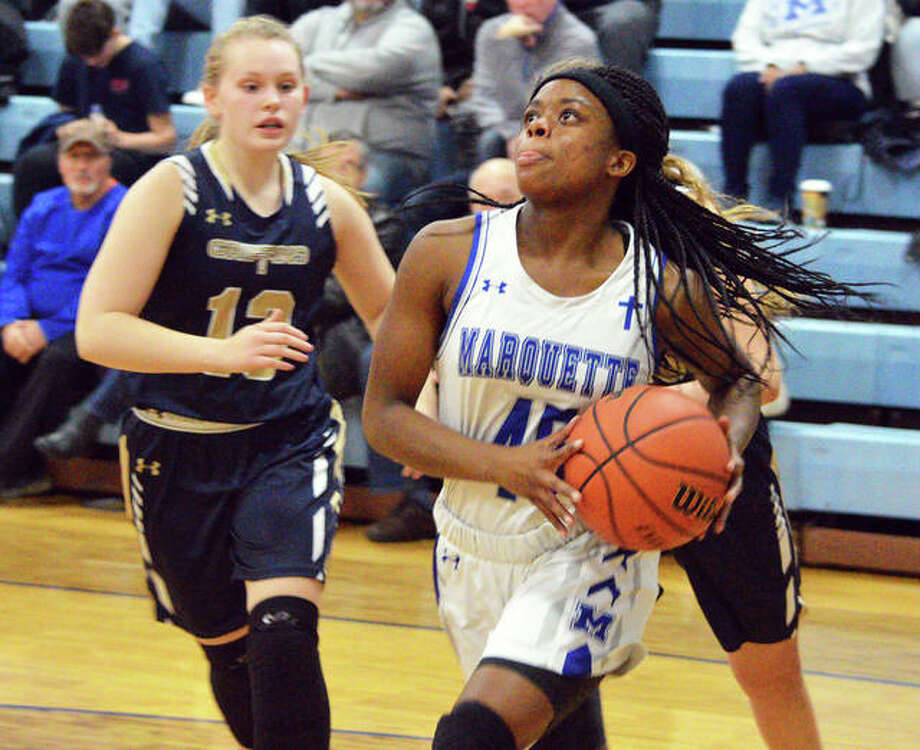 Marquette Catholic's Adrenna Snipes (right) goes to the basket after getting past a pair of Father McGivney defenders Thursday night in Alton. Photo: Scott Marion / Hearst Midwest