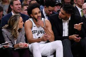 Spurs assistant coaches Becky Hammon, left, and Tim Duncan, right, give advice to guard Derrick White during first-half NBA action against the Brooklyn Nets in the AT&T Center on Thursday, Dec. 19, 2019.