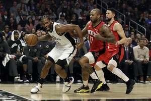 Los Angeles Clippers' Kawhi Leonard, left, is defended by Houston Rockets' P.J. Tucker (17) and Austin Rivers, right, during the first half of an NBA basketball game Thursday, Dec. 19, 2019, in Los Angeles. (AP Photo/Marcio Jose Sanchez)