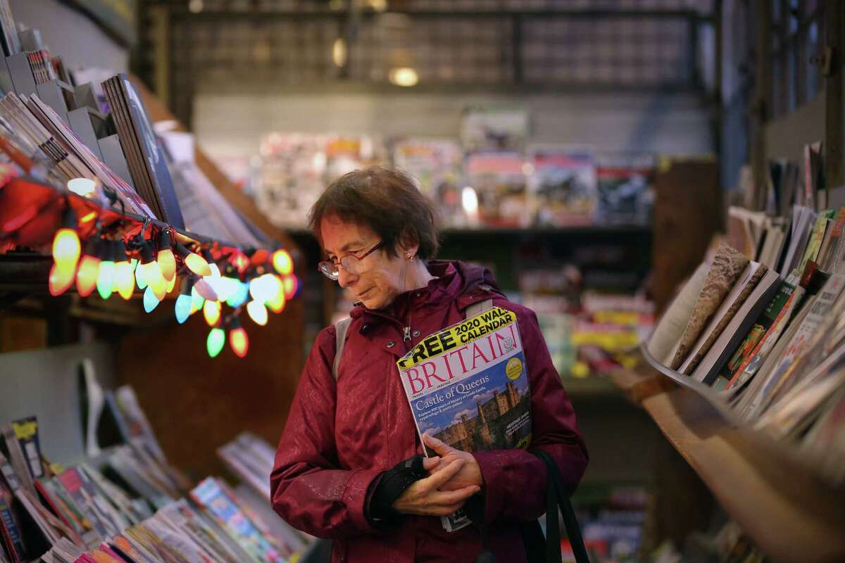 Pat Cirone browses through the magazine at First and Pike News looking for a Christmas present for her nephew. She has frequented the corner news stand for the past 30 years. The landmark shop will close down Dec. 31, 40 years after it was first opened by Lee Lauckhart.