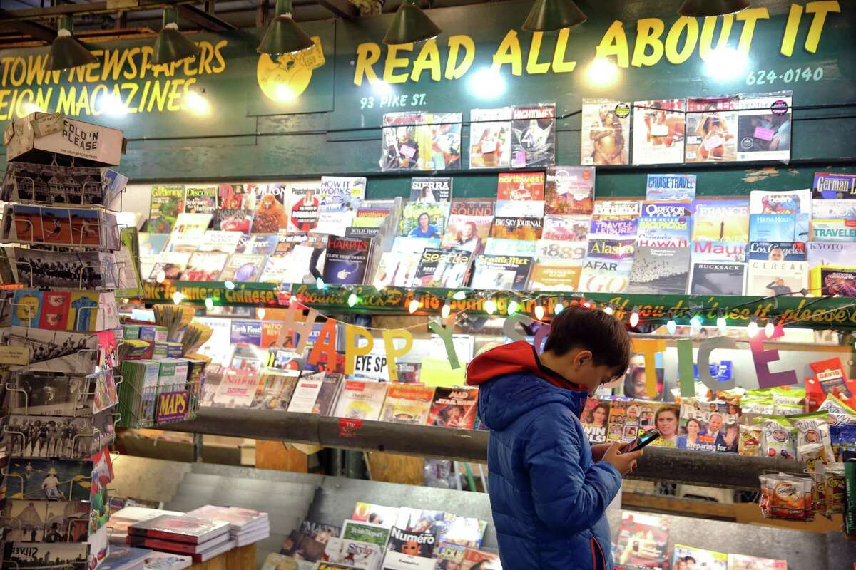 Anthony Yang, 11, is glued to his phone in front of the magazine rack at First and Pike News, Thursday, Dec. 19, 2019. Yang and his mother, who are visiting Seattle from Beijing, bought gum from the shop to stick on the gum wall. Tourists often stop at the landmark news stand to buy gum or postcards or ask for directions.