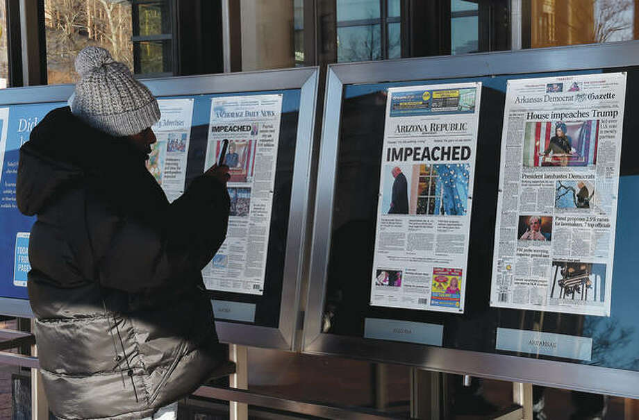 A person takes a picture of newspaper front pages on display at the Newseum in Washington, D.C., on Thursday after President Donald Trump's historic impeachment by the House of Representatives. Photo: Olivier Douliery | AFP (Getty Images)