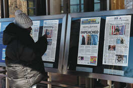 A person takes a picture of newspaper front pages on display at the Newseum in Washington, D.C., on Thursday after President Donald Trump's historic impeachment by the House of Representatives.